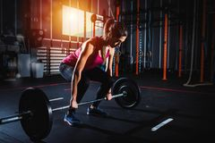 Το αθλητικό κορίτσι επιλύει στη γυμναστική με ένα barbell Στοκ Φωτογραφίες