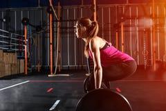 Το αθλητικό κορίτσι επιλύει στη γυμναστική με ένα barbell Στοκ εικόνα με δικαίωμα ελεύθερης χρήσης