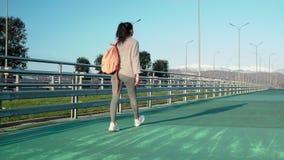 Το αθλητικό κορίτσι εφήβων περπατά στο ανοικτό αθλητικό στάδιο, η κάμερα την ακολουθεί απόθεμα βίντεο