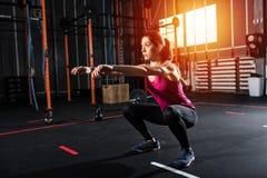 Το αθλητικό κορίτσι κάθεται οκλαδόν τις ασκήσεις στη γυμναστική Στοκ Εικόνα