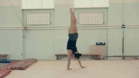 Το αθλητικό κορίτσι, στη γυμναστική, οι άνοδοι στα όπλα της, περπατούν  απόθεμα βίντεο
