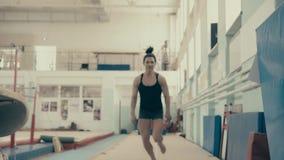 Το αθλητικό αθλητικό κορίτσι, στη γυμναστική, συσσωρεύει και κάνει το άλμα στα χαλιά απόθεμα βίντεο