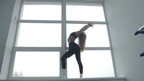 Το αθλητικό κορίτσι της Νίκαιας εκτελεί τις ασκήσεις στο σύγχρονο χορό που στέκεται σε ένα ευρύχωρο παράθυρο φιλμ μικρού μήκους