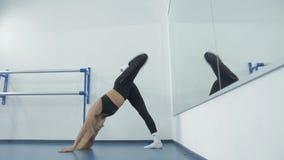 Το αθλητικό κορίτσι της Νίκαιας εκτελεί τις ασκήσεις στο σύγχρονο χορό που στέκεται σε ένα ευρύχωρο παράθυρο απόθεμα βίντεο