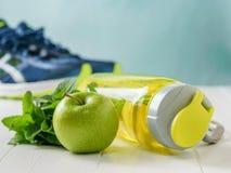 Το αθλητικό μπουκάλι με μια αναζωογόνηση πίνει και η πράσινες Apple και μια μέντα στο υπόβαθρο του τρεξίματος των παπουτσιών Στοκ φωτογραφία με δικαίωμα ελεύθερης χρήσης