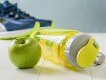 Το αθλητικό μπουκάλι με μια αναζωογόνηση πίνει και η πράσινη Apple στο υπόβαθρο του τρεξίματος των παπουτσιών Στοκ Φωτογραφία