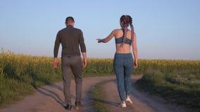 Το αθλητικό ταξίδι, ο άνδρας ζευγαριού αθλητών και η γυναίκα με τις πλεξούδες και τον αθλητισμό kanekalon λογαριάζουν το περπάτημ απόθεμα βίντεο