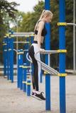 Το αθλητικό κορίτσι είναι δεσμευμένο στους φραγμούς Στοκ Φωτογραφία