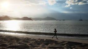 Το αθλητικό κορίτσι τρέχει στην παραλία απόθεμα βίντεο