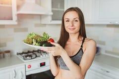 Το αθλητικό όμορφο νέο κορίτσι κάνει τη σαλάτα μετά από μια σκληρή ικανότητα workout Στοκ εικόνα με δικαίωμα ελεύθερης χρήσης