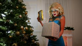 Το αιφνιδιαστικό κιβώτιο Χριστουγέννων με ένα δώρο σε μια όμορφη συσκευασία, ανοίγει την ευτυχή στάση κοριτσιών κοντά στο χριστου φιλμ μικρού μήκους
