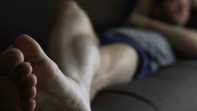 Το ακατάστατο πιωμένο αρσενικό στους μπόξερ που κοιμούνται στον καναπέ, χαλαρώνει το χρόνο του ενιαίου ατόμου στο σπίτι απόθεμα βίντεο
