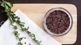 Το ακατέργαστο καφετί ρύζι στο επίπεδο τεμαχίζοντας πινάκων βρέθηκε Στοκ Φωτογραφίες