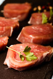 Το ακατέργαστο κρέας με τα χορτάρια και τα καρυκεύματα σε μια μαύρη πλάκα καλύπτουν σε ένα μπλε Στοκ Φωτογραφίες