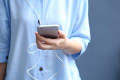 Το ακουστικό ένδυσης γυναικών με τη χρησιμοποίηση του smartphone για ακούει τραγούδι Στοκ Φωτογραφία