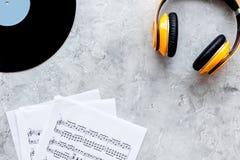 Το ακουστικό, το vynil με τη σημείωση εγγράφου στο στούντιο μουσικής για το DJ ή ο μουσικός λειτουργούν στη τοπ άποψη υποβάθρου γ Στοκ Φωτογραφίες