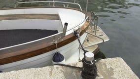 Το αλιευτικό σκάφος είναι σχετισμένο με το σχοινί για την αποβάθρα, μαρίνα απόθεμα βίντεο
