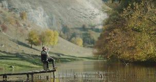 Το αλιεύοντας χρονικό άτομο έχει μια αναψυχή στη φύση, που πιάνει τα ψάρια από τη γέφυρα φιλμ μικρού μήκους