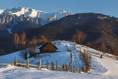 Το αλπικό τοπίο με το αγροτικά ξύλινα εξοχικό σπίτι και το χιόνι κάλυψε την κορυφογραμμή των βουνών Bucegi στο φως ηλιοβασιλέματο στοκ εικόνες
