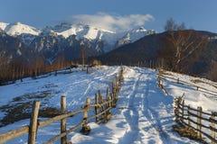 Το αλπικό τοπίο με το αγροτικά ξύλινα εξοχικό σπίτι και το χιόνι κάλυψε την κορυφογραμμή των βουνών Bucegi στο φως ηλιοβασιλέματο στοκ εικόνες με δικαίωμα ελεύθερης χρήσης