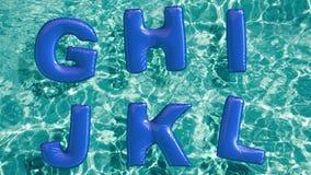 Το αλφάβητο φιαγμένο από διαμορφωμένο διογκώσιμο κολυμπά το δαχτυλίδι που επιπλέει σε μια αναζωογονώντας μπλε πισίνα απόθεμα βίντεο