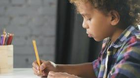 Το αμερικανικό αφρικανικό αγόρι κάθεται στον πίνακα στην τάξη και κάνει την εργασία στο σημειωματάριο εκπαίδευσης απόθεμα βίντεο