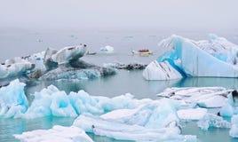 Το αμφίβιο όχημα παίρνει τους τουρίστες στο γύρο προσοχής παγόβουνων στη λιμνοθάλασσα Jokulsarlon Στοκ Εικόνες