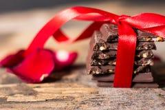 Το αμύγδαλο σοκολάτας, που δέθηκε με μια κόκκινη κορδέλλα και αυξήθηκε πέταλα Στοκ Φωτογραφίες