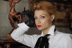 Το αναδρομικό κορίτσι καπνίζει σκεπτικά την εξέταση τη φωτογραφική μηχανή Στοκ εικόνα με δικαίωμα ελεύθερης χρήσης