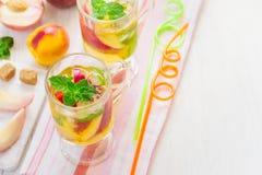 Το αναζωογονώντας καλοκαίρι πίνει το γλυκό τσάι ροδάκινων με τον πάγο και τη μέντα, κορυφή β Στοκ Φωτογραφία