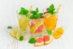 Το αναζωογονώντας καλοκαίρι πίνει το νερό με τον πάγο και το λεμόνι, πορτοκάλι και Στοκ Φωτογραφία