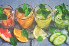 Το αναζωογονώντας καλοκαίρι πίνει το νερό με τον πάγο και το λεμόνι, πορτοκάλι, σταφύλι Στοκ Εικόνες