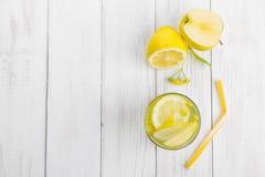 Το αναζωογονώντας ποτό για την αποτοξίνωση, νερό λεμονιών σε ένα γυαλί, φρέσκο μήλο και κίτρινος τα λουλούδια σε έναν άσπρο πίνακ στοκ φωτογραφίες