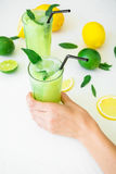 Το αναζωογονώντας ποτό με το χέρι αγγουριών, ασβέστη, πορτοκαλιών και γυναικών κρατά το γυαλί στο λευκό Στοκ φωτογραφία με δικαίωμα ελεύθερης χρήσης