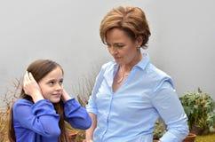 Το αναιδές κορίτσι με η μητέρα Στοκ Εικόνες