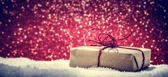 Το αναδρομικό αγροτικό δώρο Χριστουγέννων, παρόν στο χιόνι ακτινοβολεί επάνω υπόβαθρο Στοκ Εικόνες