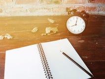 Το αναδρομικό μαύρο ξυπνητήρι, ξεραίνει τα φύλλα, το κενά σημειωματάριο και το μολύβι στον ξύλινο πίνακα Στοκ εικόνες με δικαίωμα ελεύθερης χρήσης