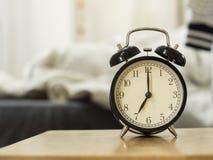 Το αναδρομικό μαύρο ξυπνητήρι παρουσιάζει 7 η ώρα το πρωί για το u ιχνών Στοκ Εικόνες