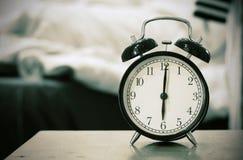 Το αναδρομικό μαύρο ξυπνητήρι παρουσιάζει 6 η ώρα το πρωί για το u ιχνών στοκ φωτογραφία