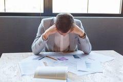 Το ανεπιτυχές άτομο κάθεται στο γραφείο με τα έγγραφα, γέρνοντας ξέφρενα το κεφάλι του Στο εσωτερικό στο γραφείο Στοκ φωτογραφίες με δικαίωμα ελεύθερης χρήσης