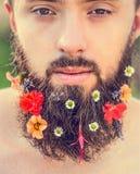 Το ανθρώπινο πρόσωπο με μια γενειάδα με τα λουλούδια στο φυσικό υπόβαθρο γενειάδων του, κλείνει επάνω Στοκ Φωτογραφίες