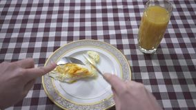 Το ανθρώπινο τέμνον αυγό χεριών που βρίσκεται στο πιάτο με το δίκρανο και το μαχαίρι, γυαλί χυμού από πορτοκάλι είναι πλησίον στο φιλμ μικρού μήκους