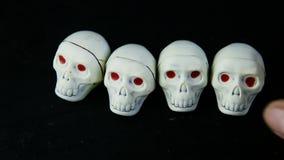 Το ανθρώπινο χέρι έβαλε πέντε άσπρες καραμέλες σοκολάτας στη μορφή κρανίων σκελετών απόθεμα βίντεο