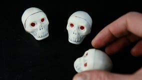 Το ανθρώπινο χέρι έθεσε τρεις καραμέλες σοκολάτας στη μορφή κρανίων σ απόθεμα βίντεο