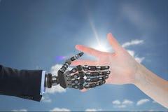 το ανθρώπινο χέρι αγγίζει το χέρι ρομπότ στο κλίμα ουρανού στοκ εικόνες