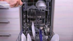 Το ανθρώπινο χέρι βάζει τα άσπρα βρώμικα πιάτα και τα μαχαιροπήρουνα σ απόθεμα βίντεο