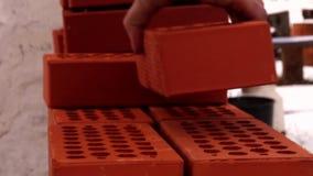 Το ανθρώπινο χέρι βάζει τα κόκκινα τούβλα απόθεμα βίντεο