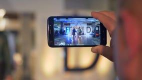 Το ανθρώπινο χέρι καταγράφει το βίντεο στο smartphone από Defile μόδας παρουσιάζει των κοριτσιών προτύπων στην εξέδρα κατά τη διά απόθεμα βίντεο