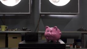 Το ανθρώπινο χέρι καταδεικνύει τον αντίχειρα κάτω πέρα από το πορτοφόλι που τίθεται στον πίνακα με τη ρόδινη piggy τράπεζα απόθεμα βίντεο