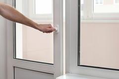 Το ανθρώπινο χέρι κλείνει μια πλαστική βινυλίου πόρτα Στοκ Εικόνες